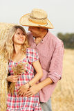 Young couple in love on haystacks in cowboy hats Stock Image