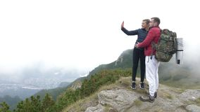Young couple in love hiking taking a selfie on mountain peak with fantastic landscape in background - stock video footage
