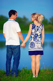 Young couple in love holding hands, near the lake Royalty Free Stock Photo