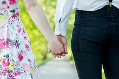 Young couple in love holding hands in summer park. Dating stock photos