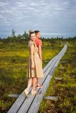 young couple in love holding hands on wooden bridge with green plants stock image