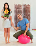 Young couple on in love at home, woman holding  flower, man sitting a ball Stock Photos