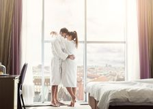 Young couple in love in hotel room in the morning. Standing at window royalty free stock images