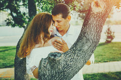 Young Couple In Love Hug Each Other In Summer Park. Enjoying Together Romantic Concept. Young men gently nudges his girlfriend near a tree in a summer park Royalty Free Stock Photography