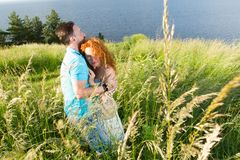 Young couple in love hugging in big green grass. Couple in love passionately hugging. Long-awaited meeting of the two lovers in fi royalty free stock photos