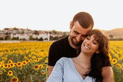 Young couple in love hugging each other in the sunflower field at sunset stock photo