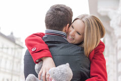 Young Couple in Love Hugging. Girlfriend Holding Teddy Bear and Smiling. Love and Valentines Day Concept. Two People royalty free stock photos