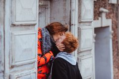 Young couple in love, hugging in the old part of town. Young loving couple hugging walking in yards of houses on the streets of old town. next to an ancient Royalty Free Stock Photo