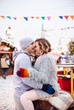 Young couple in love hugs each other and laughs at the winter Christmas eve fair stock images