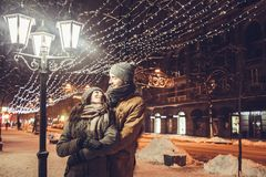 Young couple hugs under holiday winter illumination at night. Young couple in love hugs under holiday winter illumination at night Stock Photography