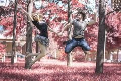 Young couple in love jumping in the air in the red forest Stock Photography