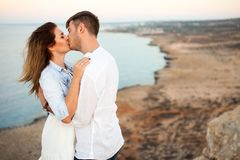 Young couple kissing on the rock with the spectacular view on the background stock photos