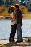 Young Couple In Love Kiss By A Lake Stock Photo