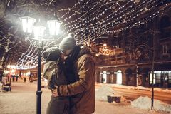 Young couple kisses under holiday winter illumination at night. Young couple in love kisses under holiday winter illumination at night Stock Images
