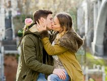 Young couple in love kissing tenderly on street celebrating Valentines day or anniversary cheering in Champagne Royalty Free Stock Image