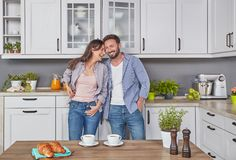 Happy couple in the kitchen. Young couple in love in the kitchen stock photos