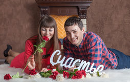 Young couple in love lies near the fireplace on carpet Royalty Free Stock Photos