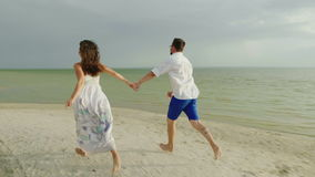 Young man and woman hold hands, run barefoot along the beach. Happy Holidays and Honeymoon. 4K slow motion video. Young couple in love in light clothes carefree stock footage