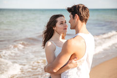 Young couple in love looking at each other and hugging. With sea at background Royalty Free Stock Photos