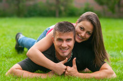 Young couple in love lying on the grass. And showing thumbs up Royalty Free Stock Images