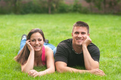 Young couple in love lying on grass and enjoying spring day Royalty Free Stock Images