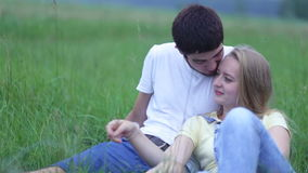 Young couple in love lying on the grass in the field, hugging and talking stock footage