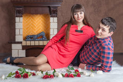 Young couple in love lying near the fireplace on carpet. Young couple in love lying near the fireplace on a white carpet with red roses stock images