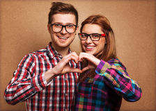 Young couple in love make a heart and hands are holding a bouque Stock Photos