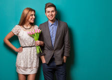 Young couple in love make a heart and hands are holding tulips. Stock Photography