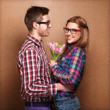 Young couple in love make a heart and hands are holding tulips. Stock Photos