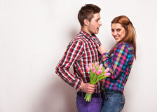 Young couple in love make a heart and hands are holding tulips. Stock Image