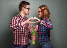 Young couple in love make a heart and hands are holding tulips. Royalty Free Stock Image