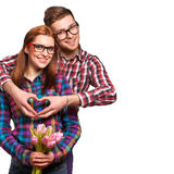 Young couple in love make a heart and hands are holding tulips. Royalty Free Stock Photo