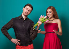 Young couple in love make a heart and hands are holding tulips. Stock Images