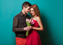 Young couple in love make a heart and hands are holding tulips. Royalty Free Stock Photography