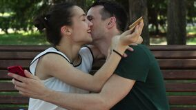 A young couple in love enter credit card details into a smartphone to pay for purchases on the Internet .