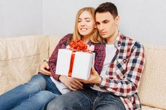 A young couple in love, a man congratulates a woman by giving her a bouquet of tulips and a gift, sitting on the sofa at home royalty free stock photography