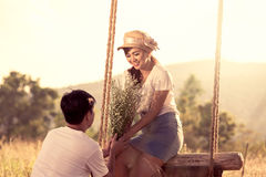 Young couple in love in the meadow field on sunny day Stock Image