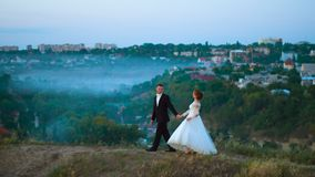 Young couple in love on a mountain meadow on the background of fog and city 4k. Young couple in love on a mountain meadow on the background of fog and city UHD stock video footage