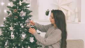 Young couple in love in new year decor with gifts and christmas tree, there is noise in the video. New Year`s decor in the room with a Christmas tree, a stock footage