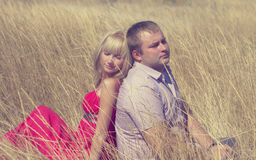 Young couple in love in the open field are sitting back to back Stock Image