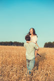 Young couple in love outdoor.Couple hugging.Young beautiful couple in love staying and kissing on the field on sunset. Stock Photos