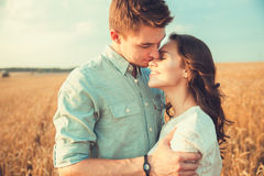 Young couple in love outdoor.Couple hugging.Young beautiful couple in love staying and kissing on the field on sunset. Stock Image