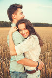Young couple in love outdoor.Couple hugging.Young beautiful couple in love staying and kissing on the field on sunset. Stock Images
