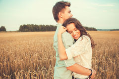 Young couple in love outdoor.Couple hugging.Young beautiful couple in love staying and kissing on the field on sunset. Young couple in love outdoor.Stunning Stock Photography