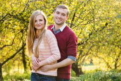 Young couple in love outdoor. Happy people walking in the woods hugging each other, having a spring mood and enjoying life Royalty Free Stock Photography