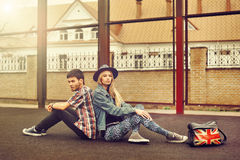 Young couple in love outdoor. Sitting back to back together. Young couple in love outdoors. Sitting back to back together Stock Image