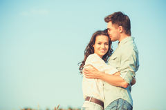 Young couple in love outdoor.Stunning sensual outdoor portrait of young stylish fashion couple posing in summer in field.Happy Smi. Ling Couple in love.They are Royalty Free Stock Image