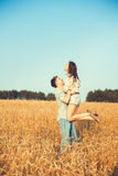 Young couple in love outdoor.Stunning sensual outdoor portrait of young stylish fashion couple posing in summer in field.Happy Smi Stock Photos