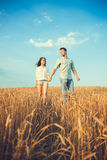Young couple in love outdoor.Stunning sensual outdoor portrait of young stylish fashion couple posing in summer in field.Happy Smi Stock Photography